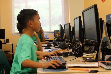 Fourth-grader Kainoa Carpenter uses the computer during class to research native Hawaiian plants. By Maile Sur.