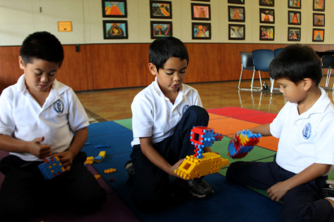 "Second graders Hanale Kauha'aha'a and Kaleikaumaka Roback, along with first-grader Errol Sheehan, play with toys at the Kamehameha Schools After School Program. They find that toys are ""what's cool."" Photo by Maile Sur."